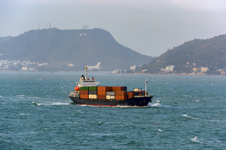Laden cargo container vessel approaching port of transshipment on delivery.