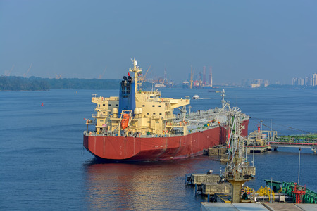 clearly: Crude oil tanker under cargo operations on typical shore station with clearly visible mechanical loading arms and pipeline infrastructure. Singapore harbour. Stock Photo