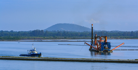 Cutter suction dredger at work of land reclamation for new ports positioned on spuds as anchors and discharge dredged soil through a floating pipeline. Johor, Southeast Asia