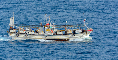 Squid fishing boat with swing booms rigged with enormous reflectorized massive arrays of big light bulbs in racks used to attract squid to the boats from deep in the ocean at night.