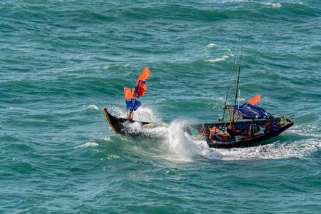 net: Small vietnamese fishing boat pounds through rough seas as it crosses the Vung Tau bay.