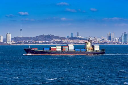 Laden container vessel approaching to port Qingdao along Jiaozhou Bay shore.