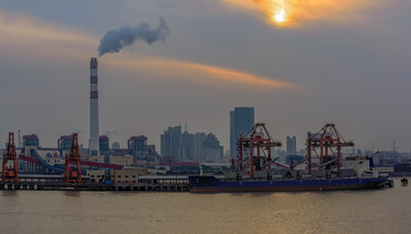 tall chimney: Bulk carrier cargo vessel moored at pier next to Chinas Biggest coal-fired power plant in Shanghai, China at twilight.