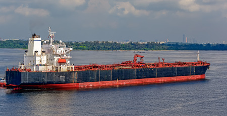Oil product tanker, passing through the Johor Strait, is approaching the Pasir Gudang oil terminal for loading. Malaysia.