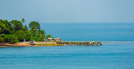 Small tropical island with stilt supported jetty at low tide Stock Photo