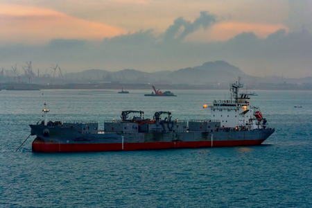 Self-discharging cement carrier vessel anchored in Singapore strait in front of Pengerang Deepwater Petroleum Terminal at twilight. Stock Photo