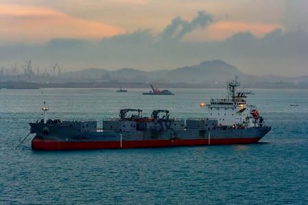 Zelflossende cementdrager vaartuig verankerd in Singapore zeestraat voor Pengerang Deepwater Petroleum Terminal bij schemering.