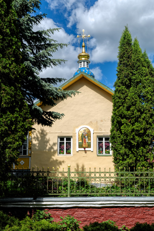 Stunning blue onion shaped church dome emblazoned with golden stars and old style golden cross on Lazarevskaya (St. Lazarus) church in famous Pskovo-Pechersky Dormition Monastery, Pskov region, Russia