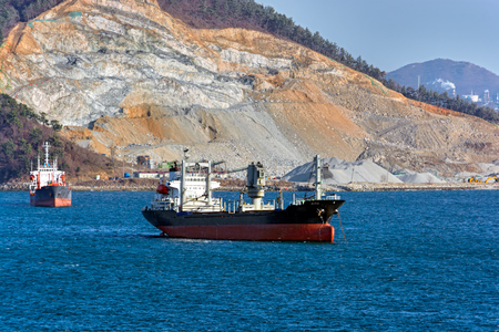 Cargo bulk vessels anchored in front of shore of the sea bay with a opencast mining quarry.