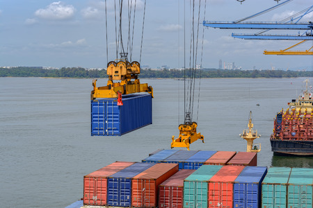 Port cargo crane lifting containers from ship moored at container terminal in Pasir Gudang, Malaysia.