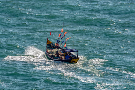 Small vietnamese fishing boat pounds through rough seas as it crosses the Vung Tau bay.