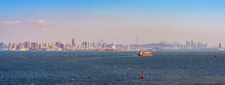 Laden container vessel leaving port Qingdao along Jiaozhou Bay shore. Stock Photo