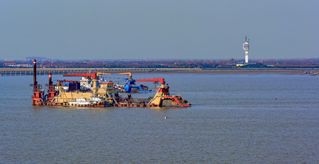 Cutter suction dredgers at work of land reclamation for new ports positioned on spuds as anchors and discharge dredged soil through a floating pipeline. Shanghai, China Stock Photo