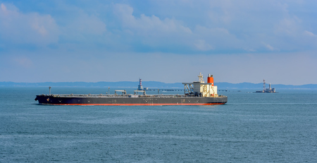 Laden crude oil tanker passes by the lighthouse in the Strait of Singapore.
