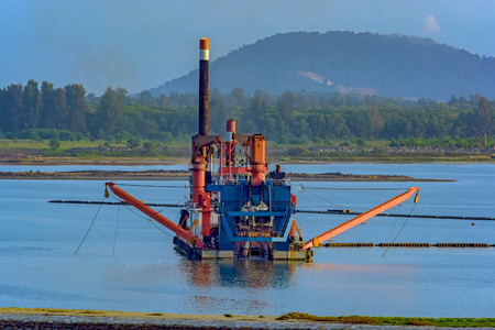 Cutter suction dredger at work of land reclamation for new ports positioned on spuds as anchors and discharge dredged soil through a floating pipeline. Singapore, Southeast Asia