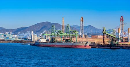 unloading: Bulk carrier ships sit berthed near a Posco steel mill at the Port of Gwangyang, Jeonnam, Korea. Stock Photo