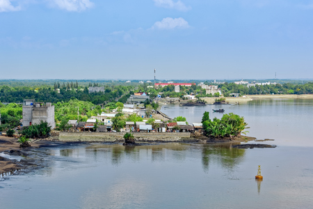 Riverside houses and shacks on stilts on Long Tau river bank in Vietnam at low tide.