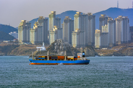 Pilot boat delivers a pilot on container ship next to Oryukdo Lighthouse and rocky coastline in Busan, South Korea.