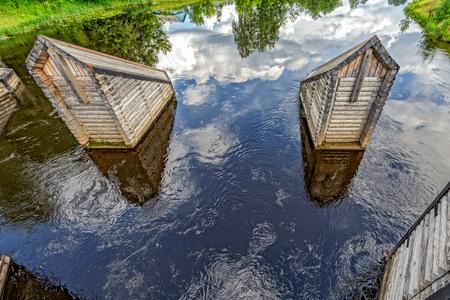 Newly restored elements of historic Tikhvin water system - wooden icebreakers before bridge. Tikhvin, Russia