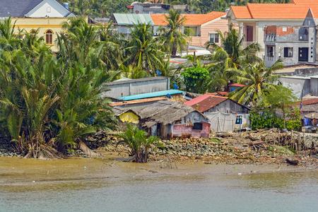 Riverside houses and shacks on stilts on Long Tau river bank in Vietnam at low tide.