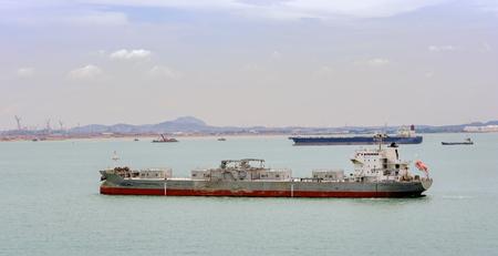 Zelflossende cementdrager vaartuig verankerd in Singapore zeestraat voor Pengerang Deepwater Petroleum Terminal.