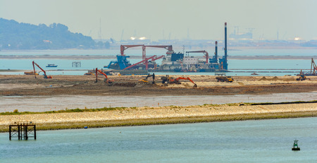 Dredging the sea fairway, panning shore and the beach to build a new commercial sea container terminal.