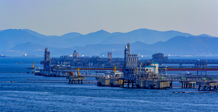 arms trade: Typical shore station used for mooring, loading and unloading oil tankers with clearly visible mechanical loading arms. Port of Gwangyang, Jeonnam, Korea.