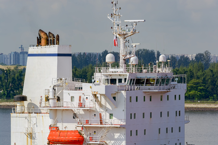 Close-up stern view to wheelhouse of a modern cargo vessel with lifeboat, communications array, radar and mannequins in sailors clothes.
