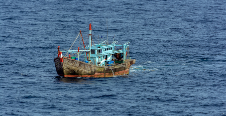 Local wooden fishing boat dragging long nets behind it in Strait of Singapore. Banco de Imagens