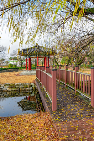 Wooden bridge to a small island with a gazebo in the middle of a pond in an autumn park