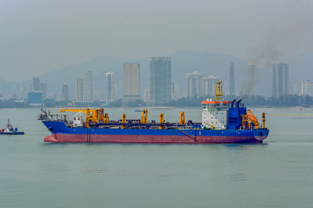 Trailing suction hopper dredger vessel anchored in front of George Town, Penang, Malaysia.
