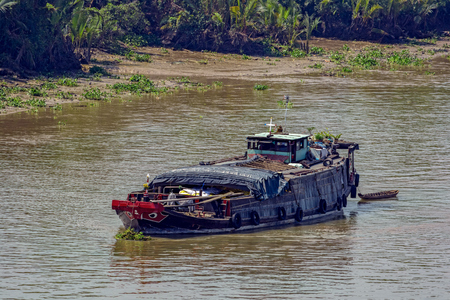 An old style wooden cargo vessel with painted eyes on the bow anchored in the Soai Rap river (Song Soai Rap) near the Ho Chi Minh City (Saigon), Vietnam to wait out low tide.