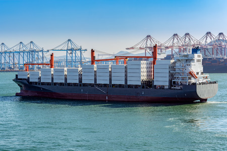 Heavy laden container ship leaving a container terminal.