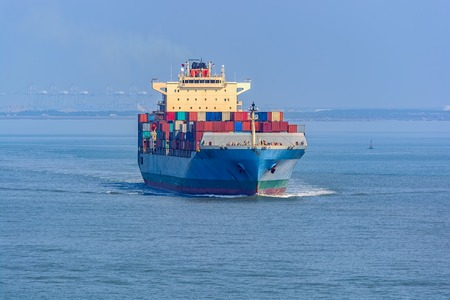 Laden cargo container vessel leaves the port of transshipment on delivery.
