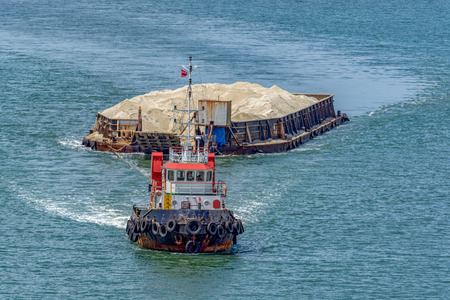 The tug boat towing a barge with sand in coastal waterway near Singapore 免版税图像