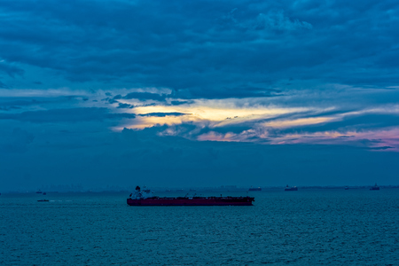 Incredible sunset over sea with a silhouette of a tanker Stock Photo
