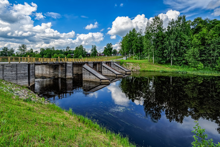 Newly restored elements of historic Tikhvin water system - levee, wooden bridge and icebreakers. Tikhvin, Russia