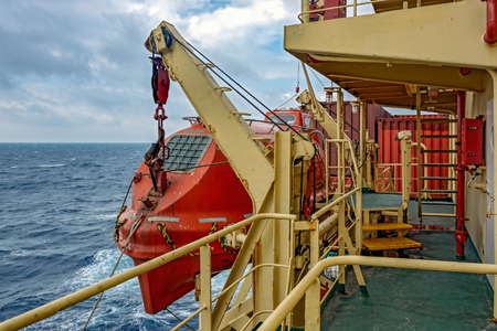 Davits holding red lifeboat on board of the container vessel. Stock Photo