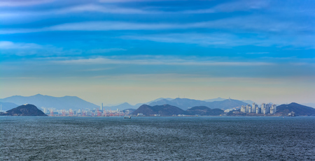 Panoramic view from Busan bay to Busan city coastline with ships, building, bridges and lighthouses Stock Photo