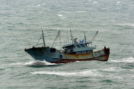 Small chinese trawler pounds through rough seas as it crosses the South China sea. Imagens