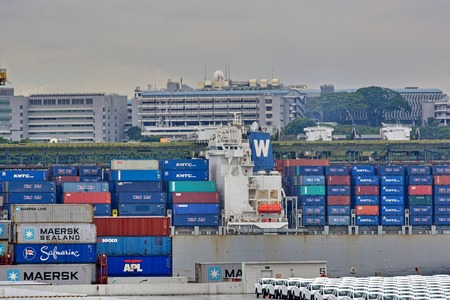SINGAPORE, MALAYSIA - Mar 01, 2017: Residential buildings behind of Port of Singapore container cargo terminal, run by PSA, one of the busiest shipping terminals in the world.