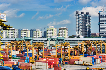 SINGAPORE - Jan 06, 2017: Colorful shipping containers are stacked at the PSA container terminal in front of multistorey residential buildings.