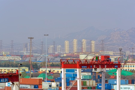 QINGDAO, CHINA - Apr 14, 2017: Qianwan container terminal with city skyline in the background at Qingdao.