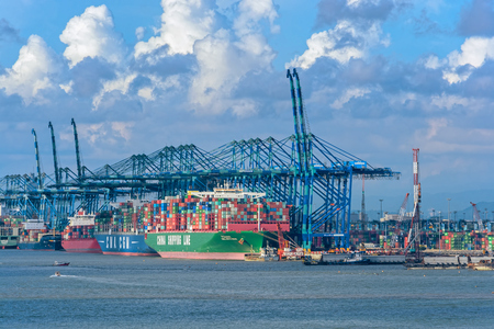 PORT KLANG, MALAYSIA - April 02, 2017: Large container gantry cranes with ships loading and unloading at Port Klang, the largest commercial port in Peninsular Malaysia.