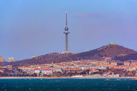QINGDAO, CHINA - Jan 20, 2017: View from sea to 232 metres tall lattice Qingdao television tower with an observation deck (1994), situated on the top of 116 metres high Taiping Hill in Julin Hill Park in Qingdao, China.