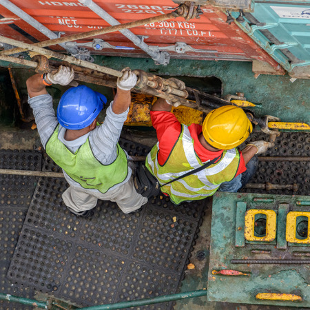 PASIR GUDANG, MALAYSIA - Feb 02, 2017: Longshoremen uses long rods with turnbuckles to secure containers on an container ship in deck sockets.