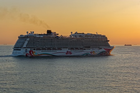 """SHANGHAI, CHINA - Nov 01, 2017: The world's fourth-biggest German-built luxury cruise liner """"Norwegian Joy"""" by NCL styled exclusively for Chinese travellers sails at sunset near Shanghai."""