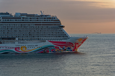 """SHANGHAI, CHINA - Nov 01, 2017: Close-up view of bow part of the world's fourth-biggest German-built luxury cruise liner """"Norwegian Joy"""" by NCL styled exclusively for Chinese travellers at sunset."""