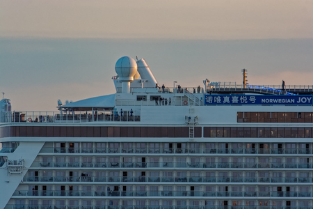 """SHANGHAI, CHINA - Nov 01, 2017: Side view of the world's fourth-biggest German-built luxury cruise liner """"Norwegian Joy"""" by NCL styled exclusively for Chinese travellers at sunset. Editorial"""