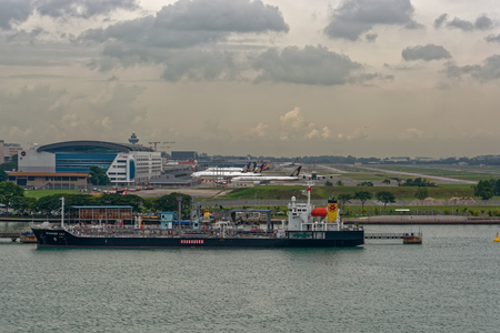 SINGAPORE STRAIT, MALAYSIA - Nov 23, 2017: Sea view to jet fuel tanker Sunrise lily berthed on pier and airplanes in front of Singapore Changi Airport buildings.